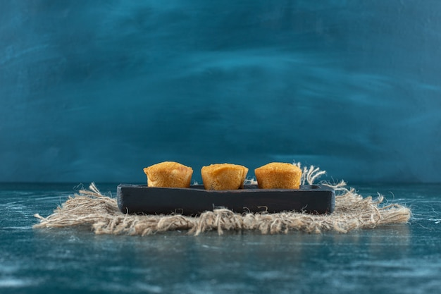 Hausgemachte kekse auf einer holzplatte auf handtuch, auf blauem hintergrund. foto in hoher qualität