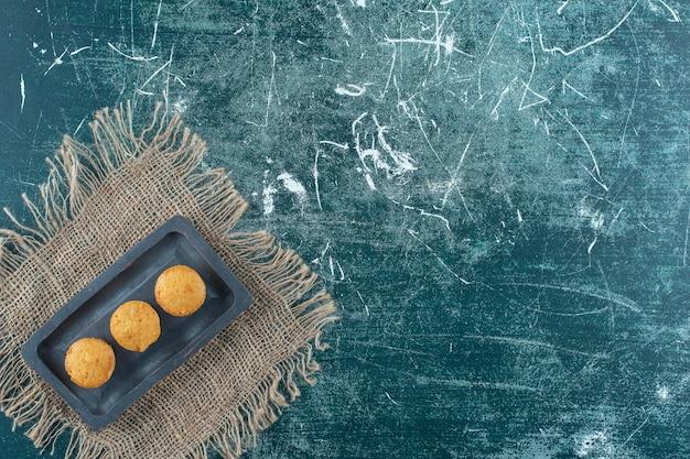 Hausgemachte kekse auf einer holzplatte auf handtuch, auf dem blauen tisch.