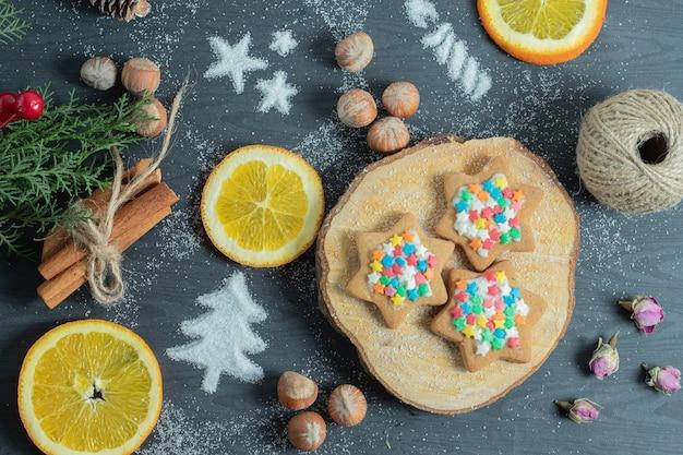 Hausgemachte kekse auf holzbrett mit verschiedenen dekorationen.