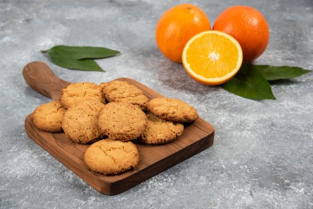 Hausgemachte kekse auf holzbrett und bio-orangen.