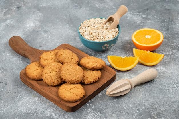 Hausgemachte kekse auf holzbrett und haferflocken mit orangen über grauer oberfläche.
