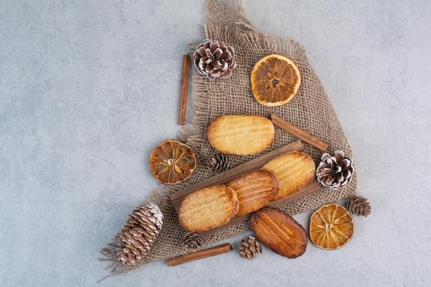 Hausgemachte kekse auf sackleinen mit tannenzapfen und trockenfrüchten. foto in hoher qualität
