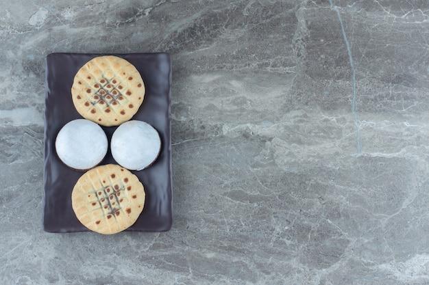 Hausgemachte kekse. frische bäckerei. auf brauner platte.