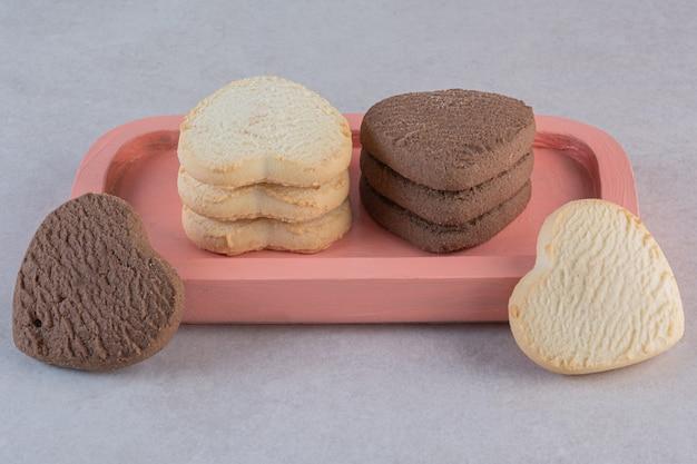 Hausgemachte kekse in einer herzform über rosa platte
