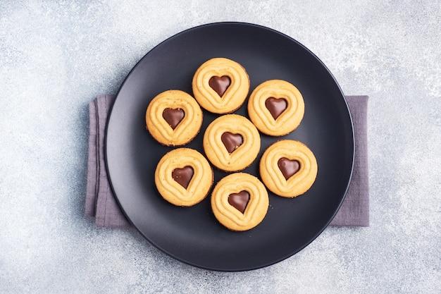Hausgemachte kekse in form von herzen auf dem teller, grauer hintergrund. konzept valentinstag. speicherplatz kopieren.