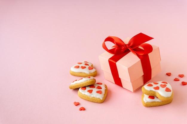 Hausgemachte kekse in form von herzen mit geschenkbox auf rosa
