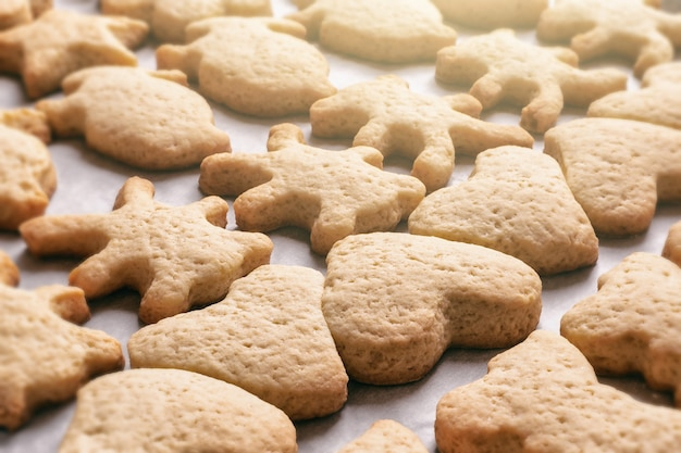 Hausgemachte kekse in form von tieren in verschiedenen formen auf pergamentpapier, weihnachts- oder neujahrsleckereien, nahaufnahme
