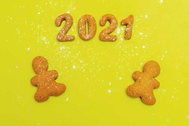 Hausgemachte kekse in form von zahlen 2021 und zwei lebkuchenmännern auf gelbem grund, draufsicht, flache lage, kopierraum. weihnachtsessen hintergrund