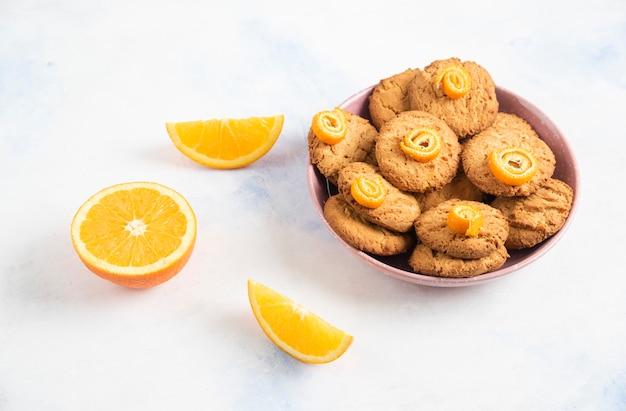 Hausgemachte kekse in rosa schüssel und orangenscheiben über weißem tisch.
