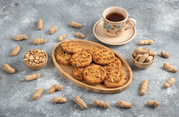 Hausgemachte kekse mit bio-erdnüssen und honig auf holzbrett mit tasse tee.