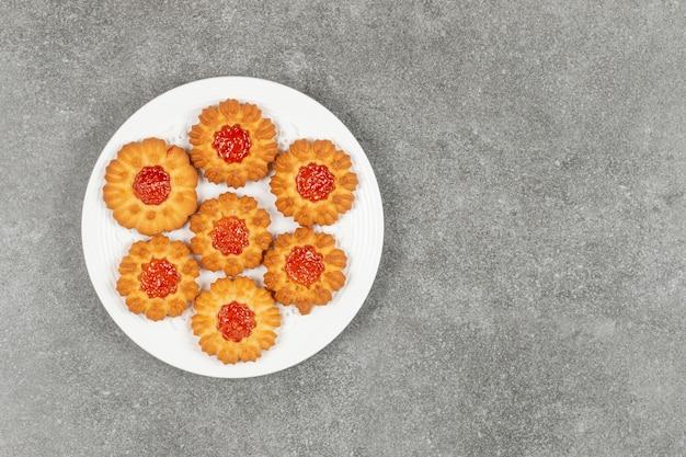 Hausgemachte kekse mit gelee auf weißem teller