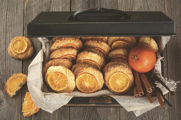 Hausgemachte kekse mit geschnittenen mandarinen und weihnachtsspielzeug in einer dunklen box. getöntes bild. selektiver fokus.