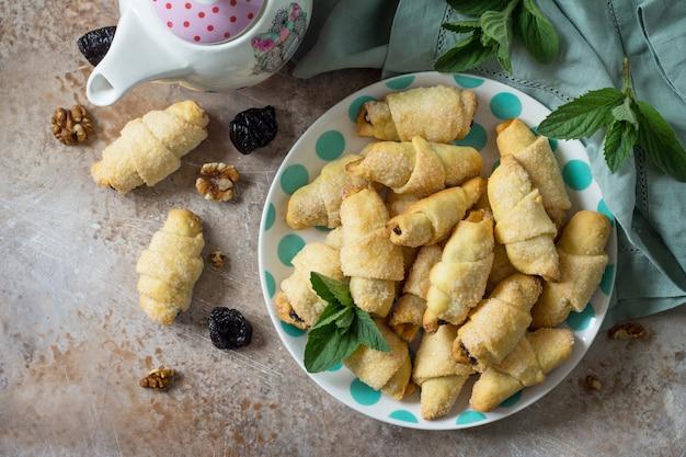 Hausgemachte kekse mit getrockneten pflaumen und walnüssen auf einem teller auf einem flachen hintergrund der tischplatte