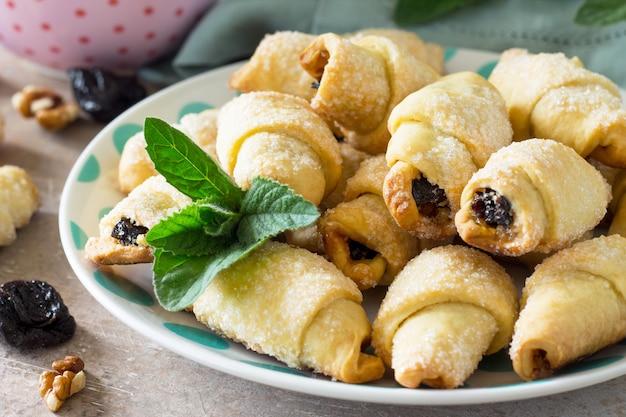 Hausgemachte kekse mit getrockneten pflaumen und walnüssen auf einem teller auf einem tisch bagels closeup