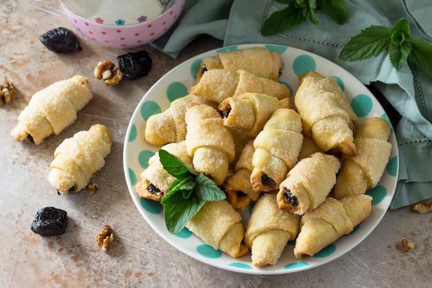 Hausgemachte kekse mit getrockneten pflaumen und walnüssen auf einem teller auf einem tisch bagels