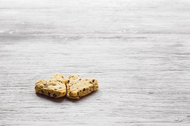 Hausgemachte kekse mit kurkuma und leinsamen in form von herz auf weißen brettern. essen zum valentinstag. seitenansicht.