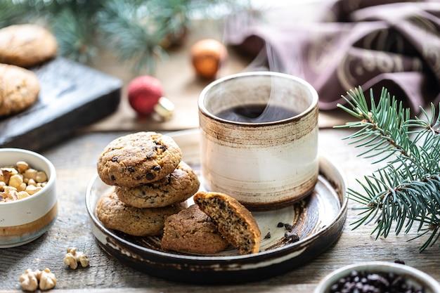 Hausgemachte kekse mit nüssen und kaffee in einer keramikschale auf einem holztisch mit spielzeug und weihnachtsbaumzweigen.