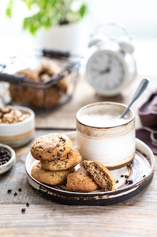 Hausgemachte kekse mit nüssen und kaffee in einer keramikschale auf einem holztisch. zeit, kaffee zu trinken. wecker im hintergrund. frühstück