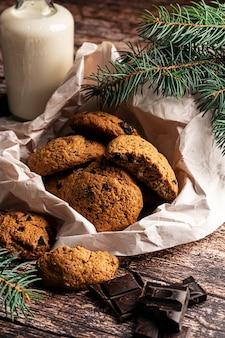 Hausgemachte kekse und milch mit schokoladenstückchen auf dunklem holzhintergrund