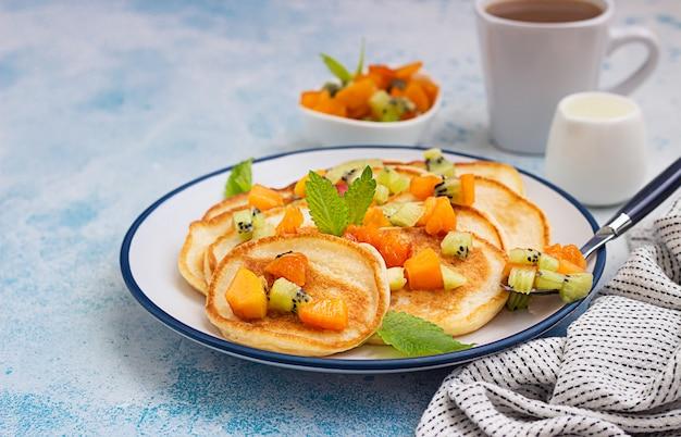 Hausgemachte klassische amerikanische pfannkuchen mit obstsalat aus aprikose und kiwi