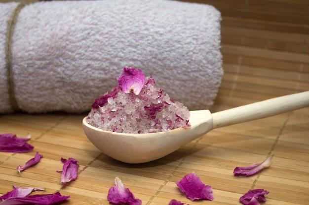 Hausgemachte körperpeeling aus meersalz und rosenblättern und pfingstrose rosa handtuch auf strohmatte