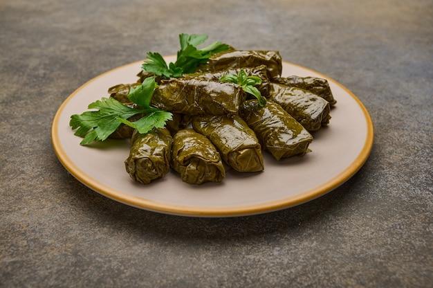Hausgemachte köstliche gefüllte weinblätter dolma mit petersilie in keramikplatte auf rostholzhintergrund