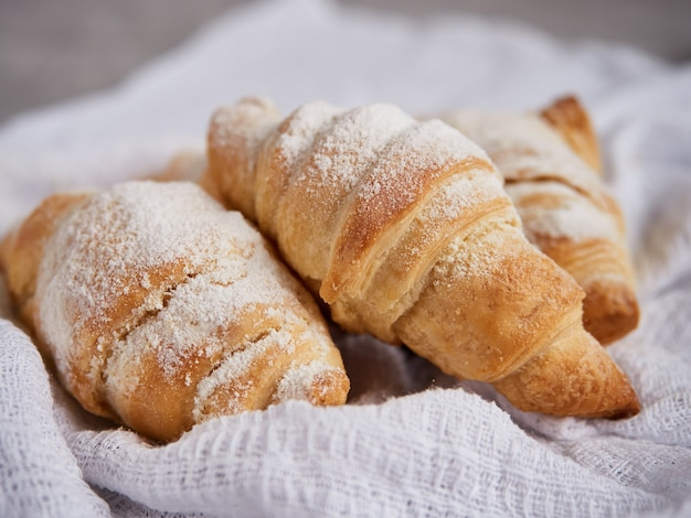 Hausgemachte kuchen, croissants mit puderzucker auf einer weißen serviette bestreut
