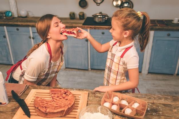 Hausgemachte kuchen kochen. eine glückliche, liebevolle familie bereitet gemeinsam eine bäckerei vor. mutter und kind tochter haben spaß in der küche. iss frischen hausgemachten kuchen