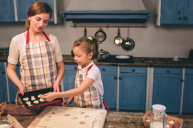 Hausgemachte kuchen kochen. eine glückliche, liebevolle familie bereitet gemeinsam eine bäckerei vor. mutter und kind tochter mädchen kochen kekse und haben spaß in der küche. kind backt kekse zusammen