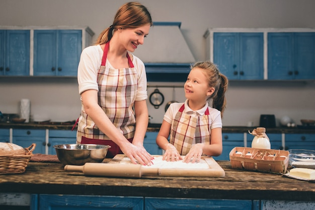 Hausgemachte kuchen kochen. glückliche liebevolle familie bereiten bäckerei zusammen vor. mutter- und kindertochtermädchen kochen plätzchen und haben spaß in der küche. rolle den teig.