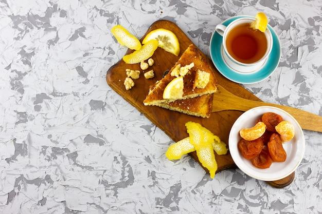 Hausgemachte kuchen mit zitronentee. wintergebäck, mit einem platz unter der inschrift. selbst gemachte zitronentorte mit winterfrucht