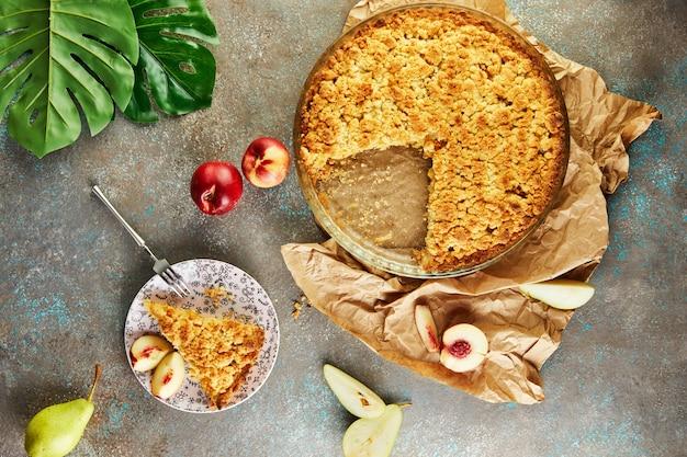 Hausgemachte kuchen, pfirsich-birnen-torte auf graublauem betonstillleben.