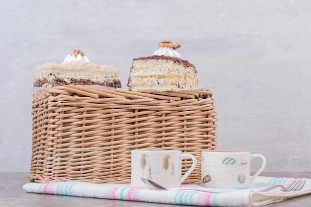Hausgemachte kuchen und tassen kaffee auf tischdecke.