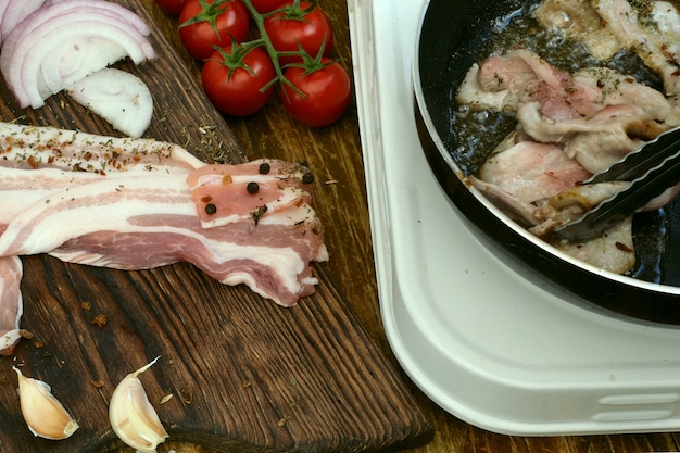 Hausgemachte küche. das braten von schweine- oder rinderbrust in einer küchenpfanne wird mit einer fleischzange gewendet. tomaten, zwiebeln, knoblauch.