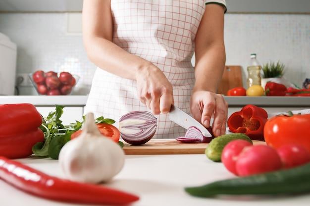 Hausgemachte küche. frau in der küche, die rote zwiebeln schneidet