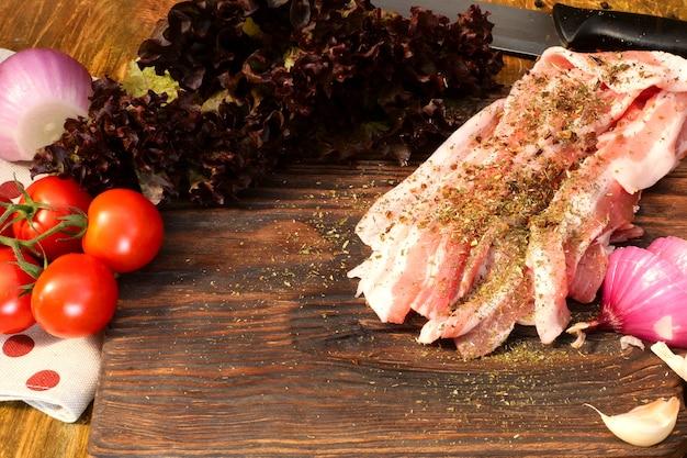 Hausgemachte küche. produkte für leckeres essen. besprühen sie mit gewürzen geschnittenes rohes schweinefleisch oder rinderbruststück auf hölzernem küchenbrett.