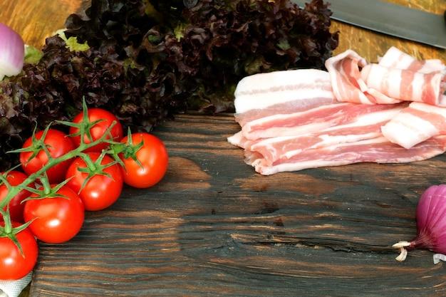 Hausgemachte küche. produkte für leckeres essen. geschnittenes rohes schweinefleisch- oder rindfleischbruststück, gemüse.