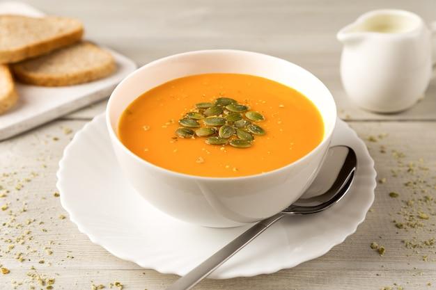 Hausgemachte kürbis-karotten-suppe in weißer schüssel mit sahne nah oben
