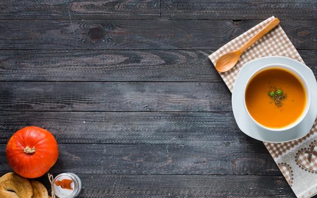 Hausgemachte kürbissuppe auf rustikalem holzuntergrund,
