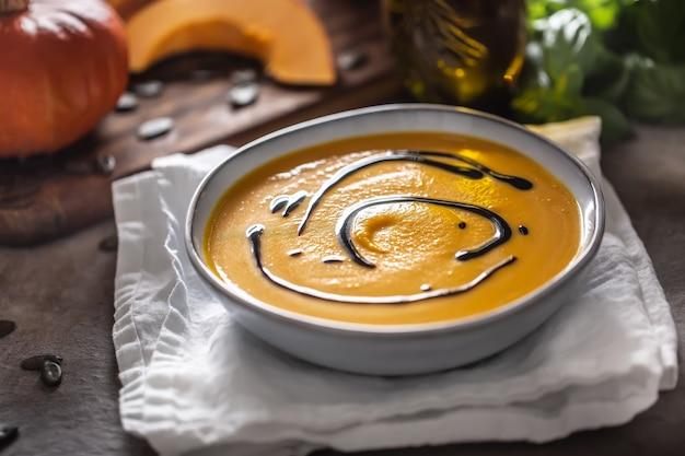 Hausgemachte kürbissuppe in schüsseln mit herbstliche hokkaido-suppe mit balsamico-essig.