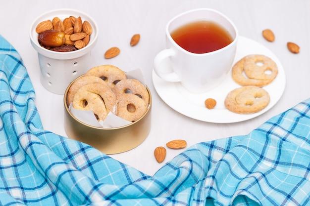 Hausgemachte lächelnplätzchen mit tasse schwarzem tee. guten morgen oder ein schönes tageskonzept. flach liegen.