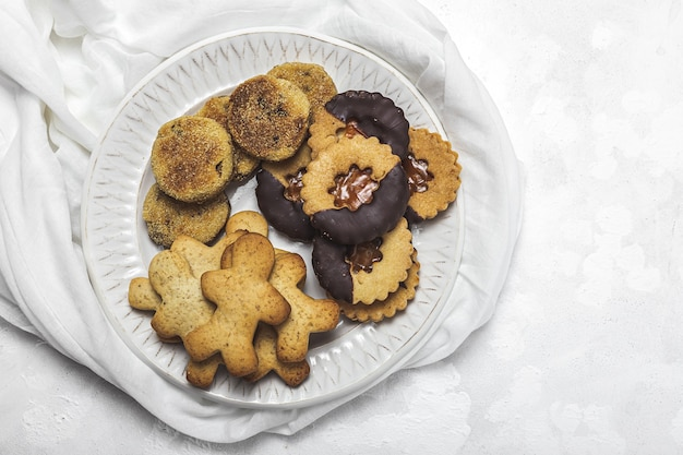 Hausgemachte lebkuchen, zimt und schokoladenplätzchen auf weißem tisch von oben. flach liegen