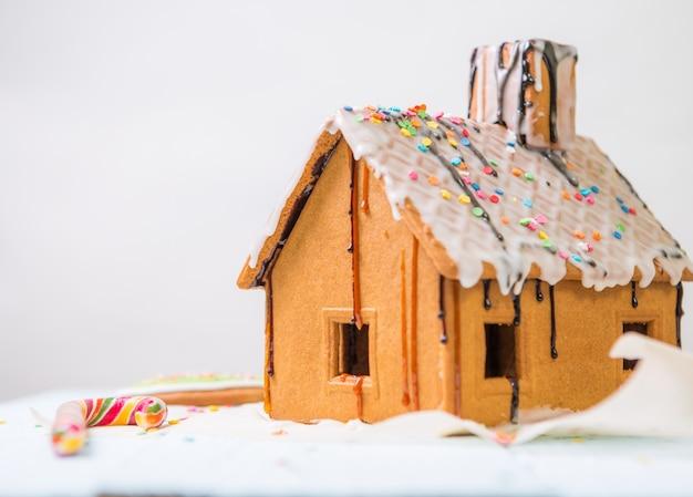 Hausgemachte lebkuchenhaus mit glasur und süßwaren bestreuen.