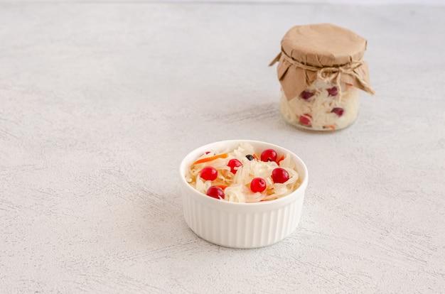 Hausgemachte leckere fermentierte milchprodukte auf einem teller sauerkraut mit preiselbeeren