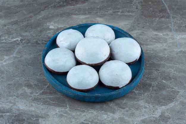 Hausgemachte leckere kekse mit weißer schokolade auf blauer holzplatte.
