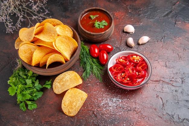 Hausgemachte leckere knusprige kartoffelchips in einer kleinen braunen schüssel ölflasche grüne tomaten knoblauchketchup und gehackter pfeffer auf dunklem tisch