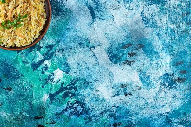 Hausgemachte leckere nudel in einer schüssel auf dem blauen tisch.