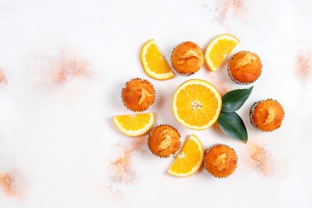 Hausgemachte leckere orangenmuffins mit frischen orangen.
