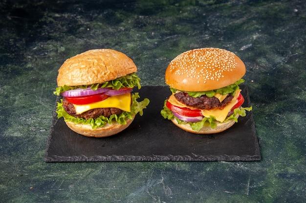 Hausgemachte leckere sandwiches auf schwarzem brett auf dunkler mischfarboberfläche