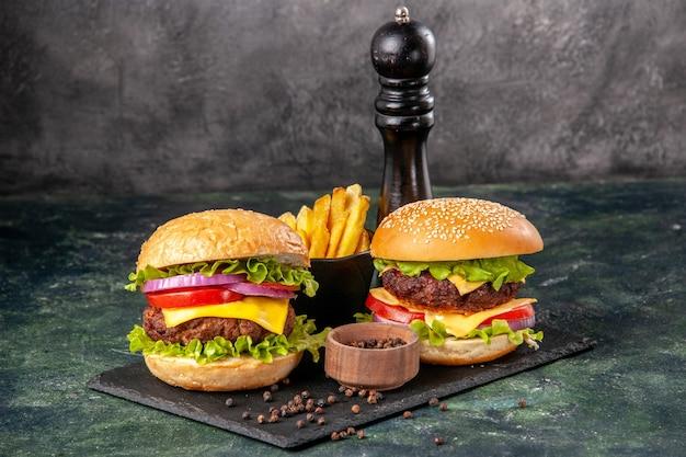 Hausgemachte leckere sandwiches auf schwarzem schneidebrett pommes ketchup auf dunkelgrauer verschwommener oberfläche